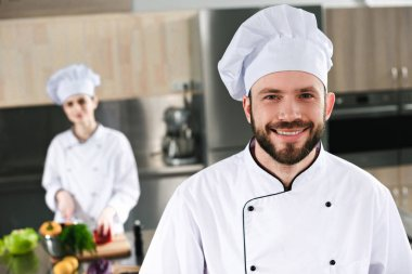 Smiling male chef in front of his female colleague on kitchen