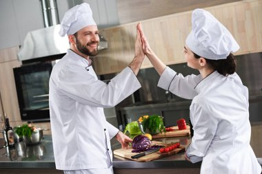Professional team of cooks giving high five by kitchen counter