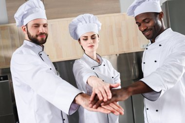 Multiracial chefs team stacking hands together on modern kitchen