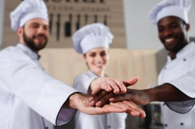 Multiracial tram of cooks stacking hands together on modern kitchen