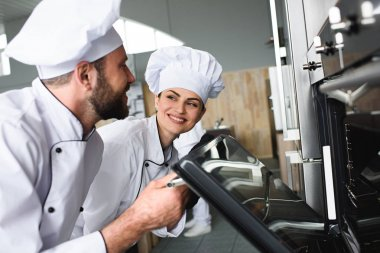 Professional chefs checking baling oven in kitchen
