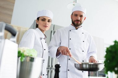 chefs with frying pan looking at camera at restaurant kitchen