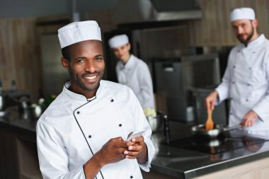 smiling african american chef using smartphone at restaurant kitchen and looking at camera