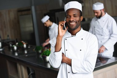 smiling african american chef talking by smartphone at restaurant kitchen