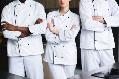cropped image of multicultural chefs standing with crossed arms at restaurant kitchen