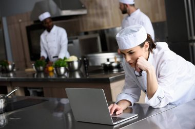 attractive chef using laptop at restaurant kitchen