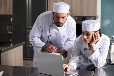 erkek ve kadın şefler lokanta mutfağı dizüstü bilgisayar kullanarak