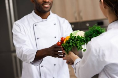 cropped image of chef giving bowl with vegetables to african american colleague at restaurant kitchen
