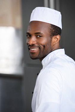 portrait of smiling handsome african american chef looking at camera at restaurant kitchen