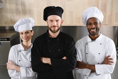 multicultural chefs standing with crossed arms and looking at camera at restaurant kitchen