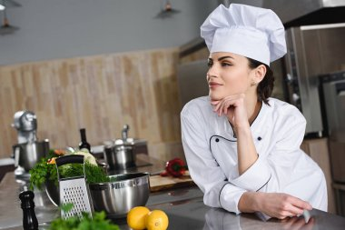 attractive pensive chef looking away at restaurant kitchen