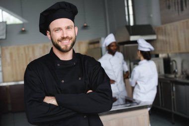 smiling chef standing with crossed arms and looking at camera at restaurant kitchen