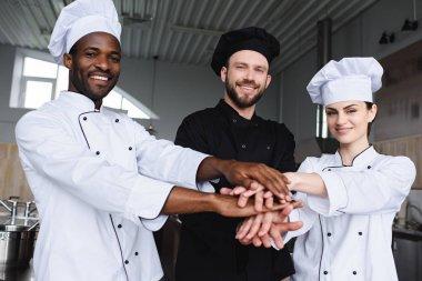 smiling multicultural chefs putting hands together at restaurant kitchen