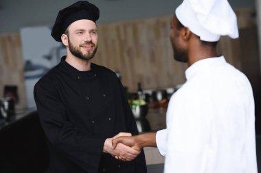 multicultural chefs shaking hands at restaurant kitchen