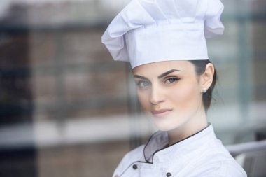 attractive chef looking at camera at restaurant kitchen