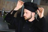 gutaussehender Koch mit Hut in Restaurantküche
