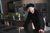 Fotografia cuoco unico bello che guarda lobbiettivo alla cucina del ristorante