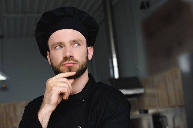 portrait of pensive handsome chef at restaurant kitchen