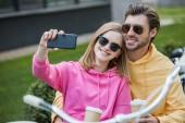 Fotografie usměvavá mladá žena v sluneční brýle s selfie s přítelem