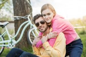 smiling young woman embracing stylish boyfriend in sunglasses