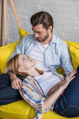 stylish young woman laying on boyfriend knees