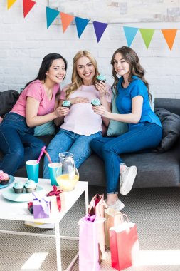 multicultural friends and pregnant woman holding cupcakes and looking at camera at baby-party