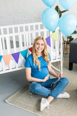 attractive pregnant woman sitting on floor and leaning on crib at baby-party