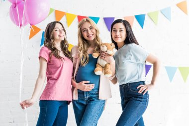 smiling multicultural friends and pregnant woman looking at camera at baby-party