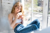 Photo happy beautiful girl sitting on windowsill with coffee cup