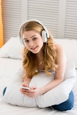 girl using smartphone and listening music with headphones while sitting on bed
