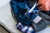 Photo close up of suitcase with clothes, passport, air ticket and airplane model