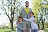 šťastné děti objímat otce v parku