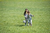 Photo little children playing football on grassy meadow in park