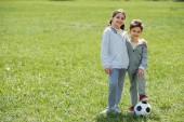 Photo happy brother and sister with ball standing on grassy meadow