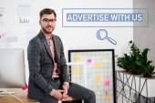 portrét mladé podnikatele v obleku a brýle sedí na stole v kanceláři, inzerovat s námi nápis