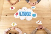 Photo overhead view of multiracial business people at wooden table with blank paper clouds, teamwork inscription
