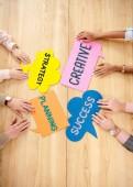 Fotografie letecké snímky mnohonárodnostní podnikatelů na dřevěný stůl s barevnými chat bubliny s strategie, plánování, kreativní, úspěch značky