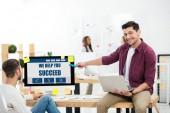 Fényképek üzletember mutatva, mi segíteni sikerül felirat a számítógép képernyőjén miközben munkahelyen dolgozó kolléga hivatalban