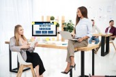 Photo selective focus of multiethnic businesswomen at workplace with we help you succeed inscription on computer screen and colleagues behind in office