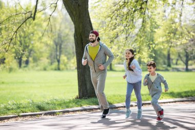 happy sportive family running on path in park
