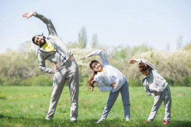 smiling father with daughter and son doing physical exercise on grassy meadow in park