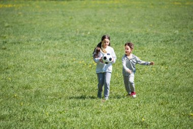 brother and sister playing football on grassy meadow