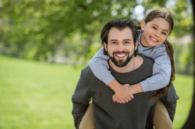 smiling father doing piggyback ride to daughter in park