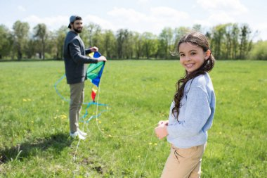 smiling daughter holding kite with father on meadow