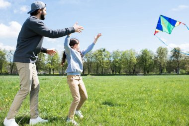 side view of daughter and father flying kite on meadow