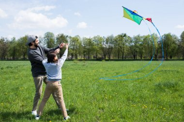 smiling father and daughter flying kite on meadow in park