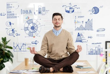 relaxed businessman with eyes closed sitting in lotus position on table in office with business graphs around