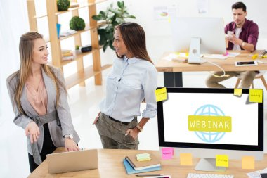 selective focus of multicultural businesswomen using laptop together at workplace in office, webinar icon on computer screen