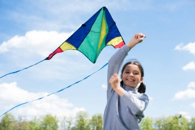 low angle view of smiling child holding kite in park