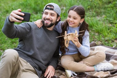 father taking selfie with daughter holding wooden toy plane on plaid in park
